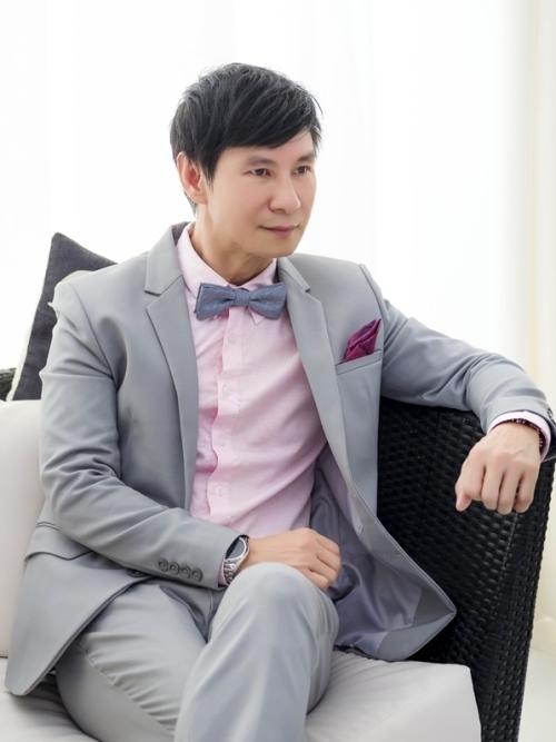 Anh thay đổi style khi phối vest xám nhạt với sơ mi hồng.