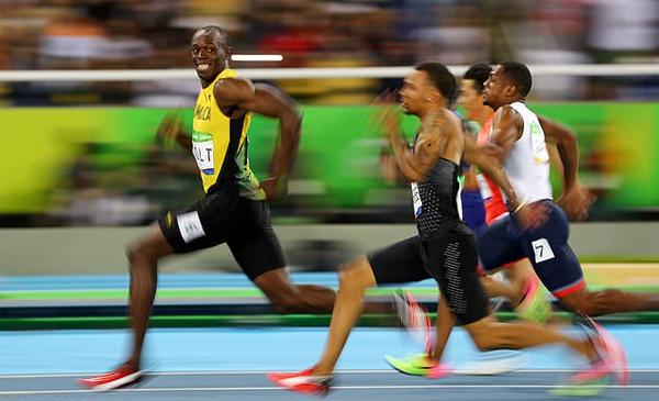 Usain Bolt và khoảnh khắc nổi tiếng khi vừa chạy về đích vừa cười ngoái nhìn đối thủ tại bán kết 100m ở Olympic Rio 2016. Ảnh: Reuters.