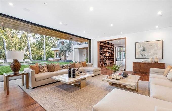 Tường kính giúp xóa nhòa khoảng cách bên trong và ngoài ngôi nhà, mang ánh sáng tràn ngập vào các căn phòng.