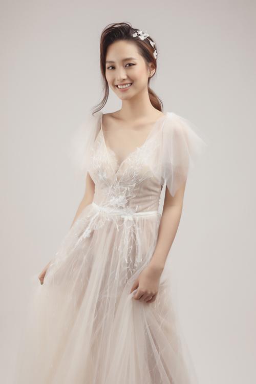 Khi diện váy cưới chữ A để chào bàn, chụp ảnh cưới, cô dâu có thể biến hóa với kiểu tóc chải lệch, buộc thấp và dùng phụ kiện bờm kết hoa.