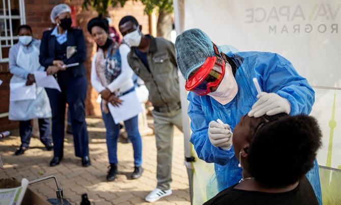 Một y tá đang lấy mẫu bệnh phẩm để làm xét nghiệm nCoV cho người nghi nhiễm ở thành phố Johannesburg, Nam Phi. Ảnh: AFP.