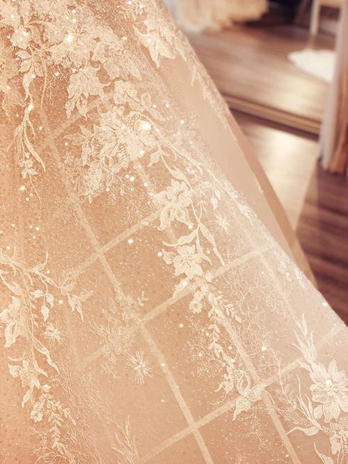 Váy được may bằng loại vải ren dệt cùng những sợi đá li ti có khả năng bắt sáng tối đa.