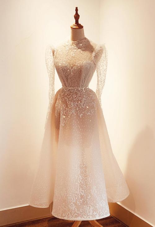 Một thiết kế khác của bà tiên váy cưới Phương Linh tôn vinh nét thanh lịch, dịu dàng cho nàng dâu Á đông. Thiết kế cổ ba phân, tay dài và ngực áo corset có thể dễ dàng che đi các khuyết điểm cơ thể của cô dâu. Kiểu váy chữ A được xem là lựa chọn hoàn hảo cho mọi dáng người.