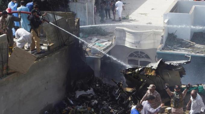 Các nhân viên cứu hộ xịt nước vào mảnh vỡ của chiếc máy bay lao xuống khu dân cư ở Karachi, Pakistan, ngày 22/5. Ảnh: AFP.