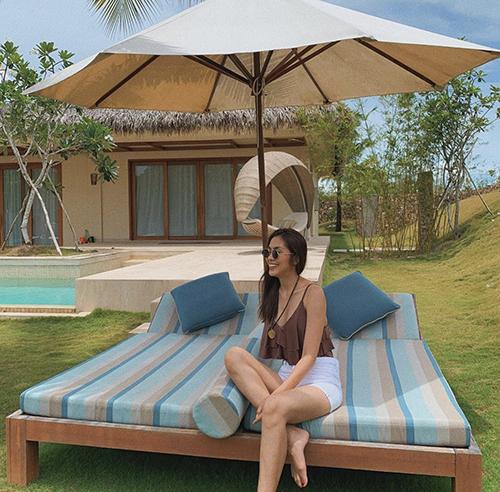 Phong cách tự do và thoái mái của Tăng Thanh Hà khi đi nghỉ dưỡng với set đồ gồm áo hai dây bèo nhún, short jeans kiểu lưng cao.