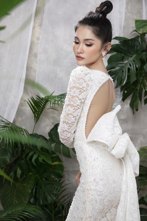 Toàn bộ thân váy là họa tiết hoa mẫu đơn đan lưới nổi bật, lưng váy có khoảng cut-out với nơ to bản, níu giữ ánh nhìn.