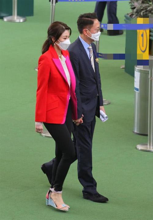 Lý Gia Hân mặc trẻ trung, sắc màu, tay nắm tay chồng rất tình tứ. Cặp đôi có thói quen nắm tay nhau mỗi khi xuất hiện trước đám đông.