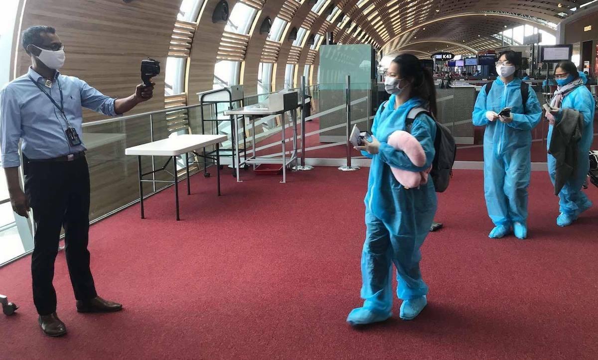Hành khách đo thân nhiệt trước khi lên chuyến bay VN8. Ảnh: VNA