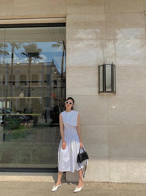 Yến Nhi thanh lihjc với nguyên set đồ trắng gồm đầm liền thân, mắt kính gương tròn, giày mullet. Cô chọn thêm túi Balenciaga màu tương phản để phối đồ.
