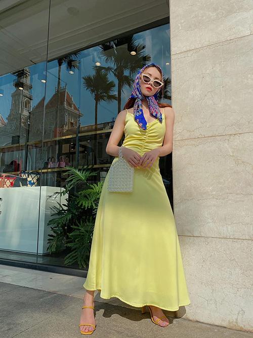 Đầm maxi màu vàng rực rỡ được Yến Trang sử dụng cùng sandal quai mảnh, túi kết cườm kiểu dáng đậm chất nữ tính.