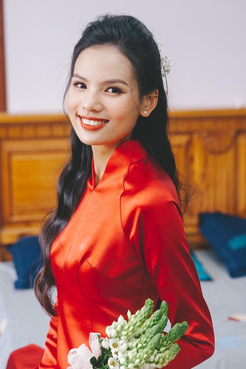 Trong ngày trọng đại, top 5 hoa hậu hoàn vũ 2017 chọn lựa tông makeup cổ điển với màu cam đỏ, lớp nền trong trẻo tôn nhan sắc thanh tú. Chị chọn kiểu tóc xoăn nhẹ, búi xoã kết hợp với áo dài đỏ không hoạ tiết.