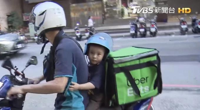 Cậu bé được bố cho đội mũ bảo hiểm, ngồi sau lưng bố, phía sau là thùng đựng đồ ăn. Ảnh: TVBS.