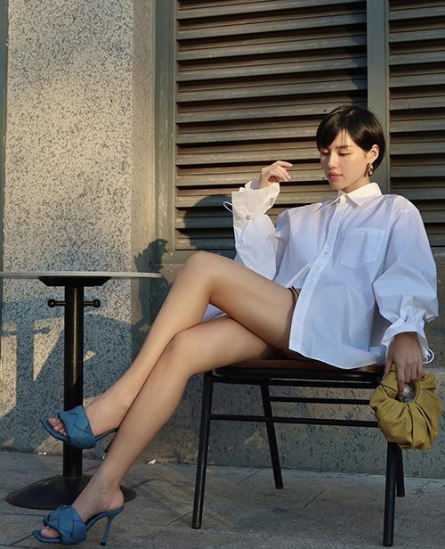 Sơ mi dáng rộng còn được Khánh Linh phối cùng short ngắn để theo đuổi mốt giấu quần.