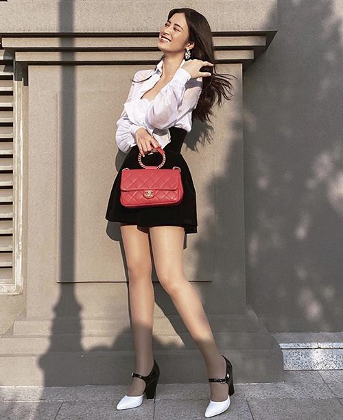 Sơ mi biến tấu với chiếc nơ bướm to bản được Đông Nhi mix ăn ý cùng kiểu quần váy màu tương phản. Ca sĩ chọn nguyên bộ phụ kiện gồm túi xách và giày Chanel để tạo điểm nhấn.
