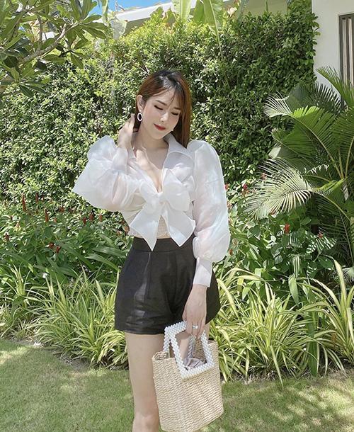 Set đồ đậm chất mùa hè của Diệp Lâm Anh với sơ mi vai bồng, quần short vải linen đen và túi cói thân thiện môi trường.