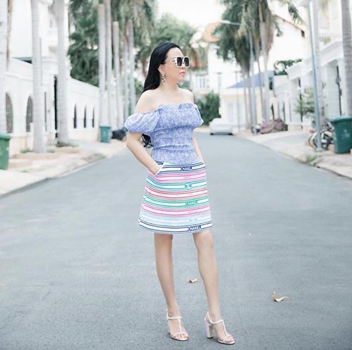 Chân váy Chanel kẻ sọc với nhiều tông màu sáng được nữ doanh nhân sử dụng cùng kiểu áo trễ vai, tay bồng điệu đà.