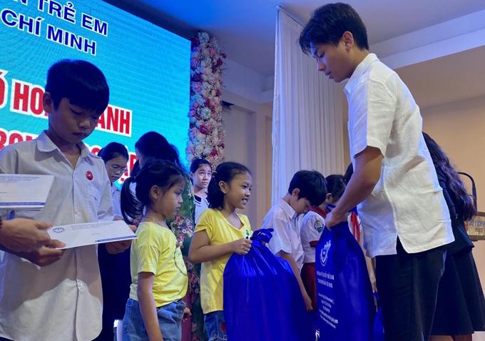 Em trai cô - Hiếu Nguyễn cũng diện áo sơmi trắng cộc tay, quần tây ân cần trao từng phần quà cho các em học sinh nghèo.