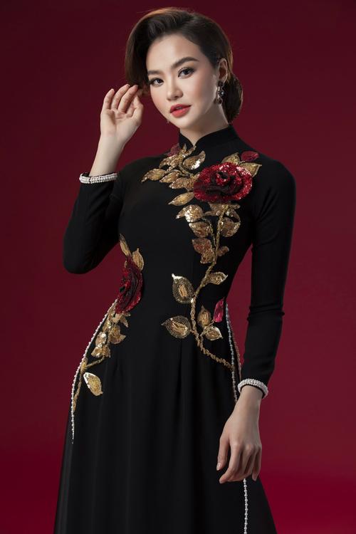 Tà áo được làm điệu với hàng cúc ngọc trai nơi viền tay áo, dọc tà.