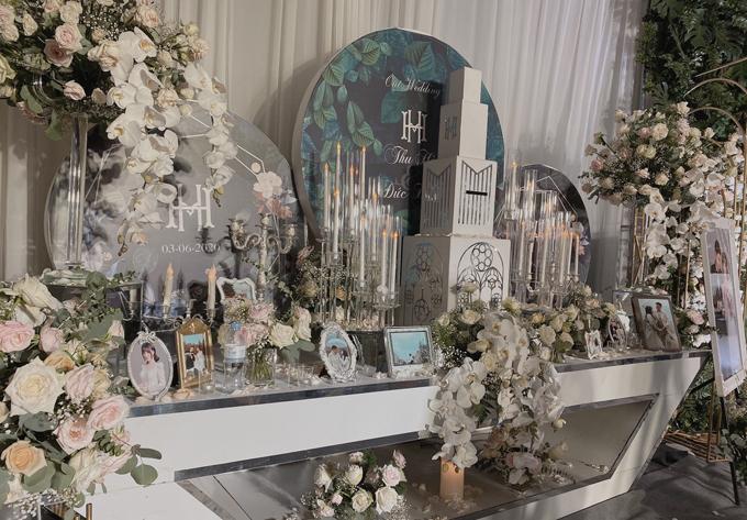 Bàn gallery mang gam trắng lãng mạn, được bày biện với nhiều hoa tươi và ảnh cưới của cặp cô dâu, chú rể.
