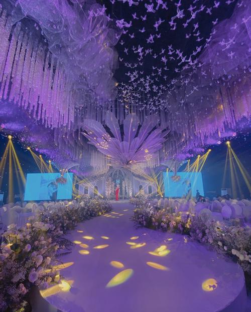 Hội trường cưới hướng tới phong cách rustic lãng mạn với điểm nhấn là trần nhà có dàn hoa treo ngược, các cánh chim 3D ngụ ý đôi uyên ương sum vầy, hòa hợp.