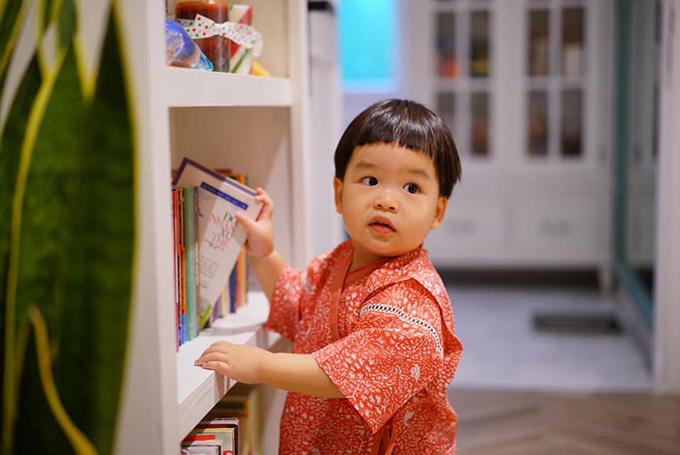 Bé Tuấn Khang, con trai Lê Khánh - Tuấn Khải, thích thú với giá sách trong nhà.