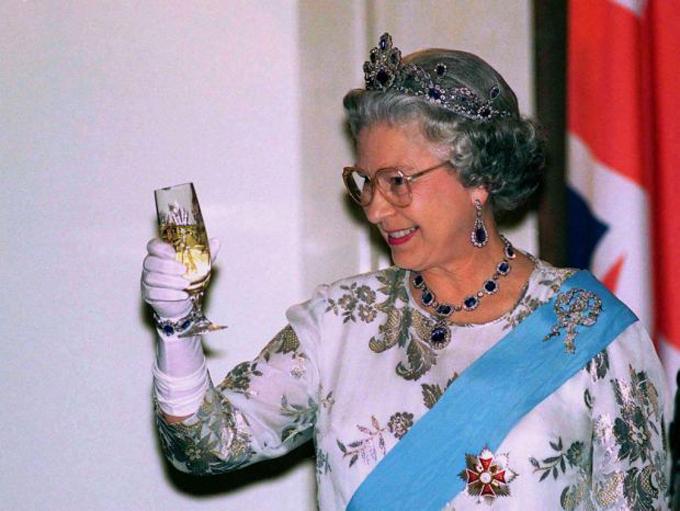 Nữ hoàng Anh uống rượu vang trong một buổi tiệc. Ảnh: UK Press.