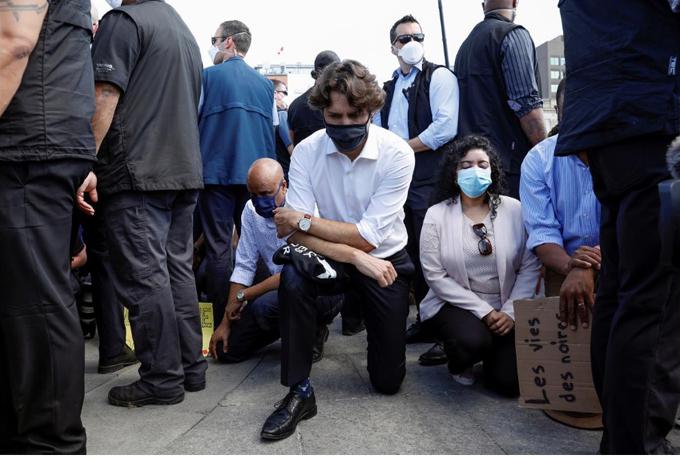 Thủ tướng Canada quỳ gối cùng người biểu tình trước tòa nhà quốc hội ở Ottawa. Ảnh: Reuters.
