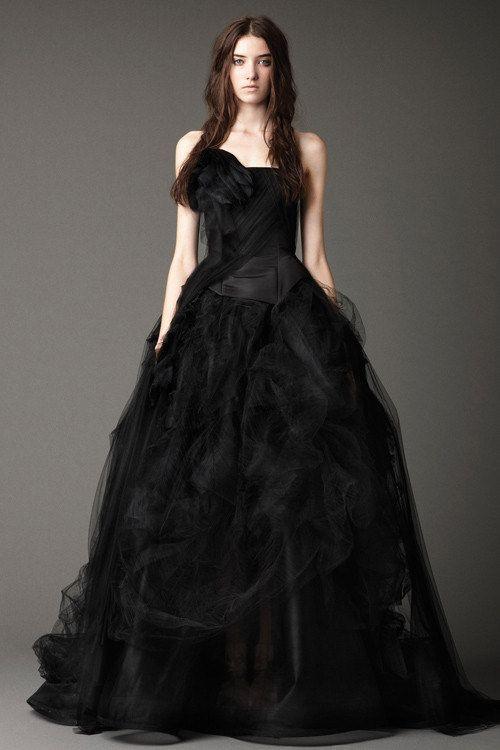 Bộ đầm đen có kết cấu bất đối xứng, phần nửa trên của váy điểm khối hoa 3D làm điểm nhấn. Phía thân váy là các khối vải xếp với bố cục ngẫu hứng, mang phom dáng xòe phồng.