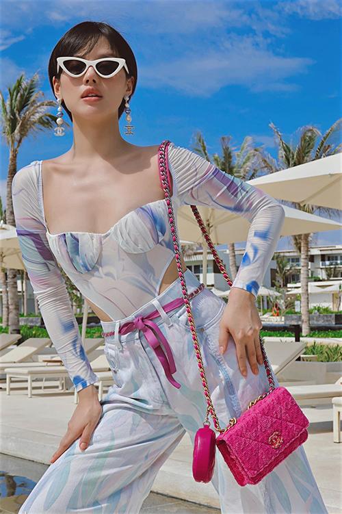 Mẫu áo thun ôm lấy cảm hứng từ kiểu bikini liền thân được Khánh Linh mix-match ăn ý cùng quần jeans lưng cao. Fashionista chọn thêm túi Chanel gam hồng để tăng sức hút cho set đồ.