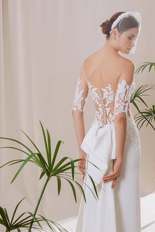 Điểm nhấn của váy chính là chiếc nơ to bản sau lưng quét đất, dành cho những cô dâu thích sự cổ điển, lãng mạn và gợi cảm.