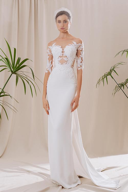 NTK cộng nét thanh lịch, cổ điển của thập niên 1970 vào váy cưới hiện đại, tạo nên điểm nhấn riêng cho từng bộ váy. Đầm Julia có dáng ôm suông, kế hợp vải crepe và tulle, khoảng cut out nơi ngực tạo hình trái tim tinh tế.