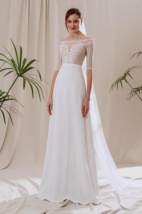 Váy Deliacó vai ngang được làm từ vải ren, trang trí bởi chi tiết hoa thêu li ti và sọc lưới. Sự tối giản được đem vào thiết kế với tùng váy chữ A, chất liệu crepe gân trắng trơn. Váy tạo hiệu ứng thị giác giúp vòng eo thon gọn.