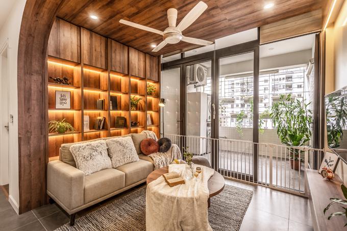 Phòng khách được trang trí theo phong cách đơn giản, hiện đại. Điểm nhấn của phòng khách là hệ tủ sách phía sau bộ sofa, giúp nhà hạn chế nội thất, tối ưu diện tích sử dụng. Việc lựa chọn đồ nội thất gỗ tự nhiên, sofa chân thấp, bàn trà gỗ tạo ấn tượng cho phòng khách.