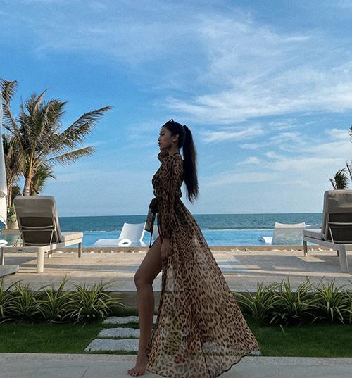 Tiên Nguyễn khoe nét cá tính và sexy khi sử dụng áo choàng hoạ tiết da beo để mix cùng bikini liền thân tông đen.