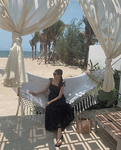 Đầm hai dây thắt nơ điệu đà đi cùng chi tiết xếp tầng và phom tạo sự thoải mái được hoa hậu Phương Khánh sử dụng khi đi nghỉ dưỡng.
