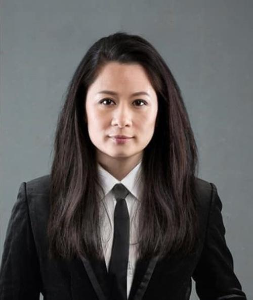 Bằng Kiều mang dáng dấp của một nữ luật sư khi mặc vest đen, đeo cà vạt và buông tóc. Gương mặt vuông vắn của anh bầu bĩnh hơn nhờ các chức năng chỉnh ảnh.