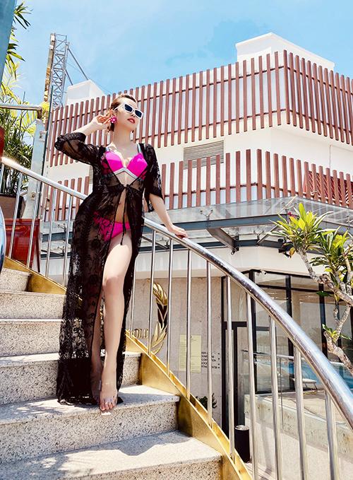 Trang phục dạo biển của Jennifer Phạm trở nên điệu đà hơn với áo choàng ren, giày cao gót quai nhựa và khuyên tai màu đồng điệu với bikini.