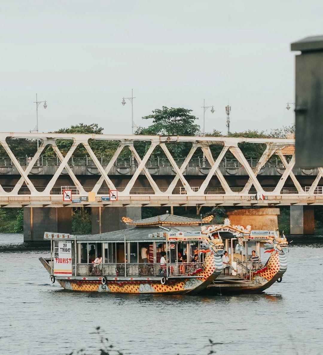 Nhiều du khách thích ngồi thuyền rồng nghe ca Huế trên sông Hương. Phía sau là cầu đường sắt Bạch hổ và cầu Dã Viên.