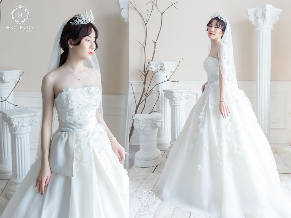 Chiếc váy từ thương hiệu cao cấp Vera Wang sở hữunhững bông hoa 3D được khâu kết tỉ mỉ khắp thân áo và tạo điểm nhấntrẻ trung vớichiếc nơ lụa bên hông.