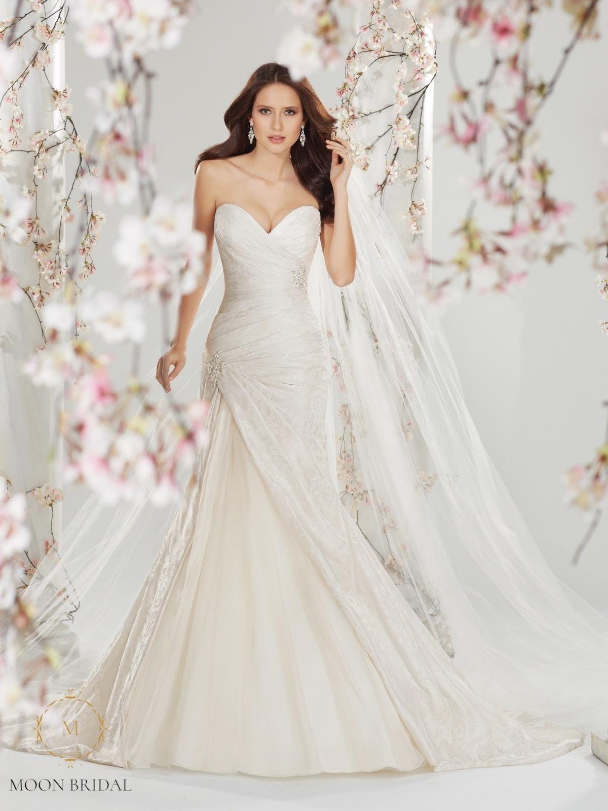 Mẫu váy cưới Cersei của nhà nổi tiếng thế giới Sophia Tolli là sự kết hợpgiữa kỹ thuật xếp nếp, phom dáng chữ A mềm mại và chất liệu gấm brocade cao cấp. Hai chiếc brooch pha lê cao cấp ở eo và hông giúp chiếc váy có thêm điểm nhấn nữ tính, điệu đà.