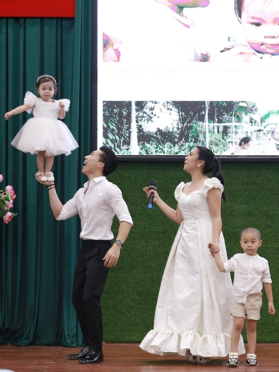 Khác với anh, Mì Mí có phần rụt rè hơn khi đứng trước đám đông. Quốc Nghiệp và vợ phải pha trò, động viên con gái hoàn thành phần biểu diễn.