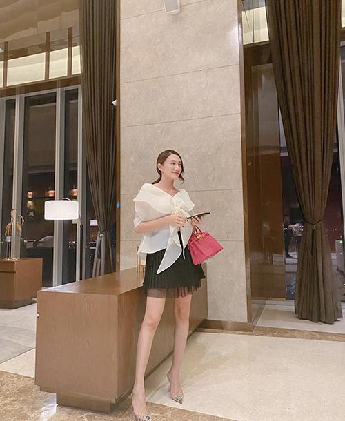 Áo blouse cách điệu, chân váy xếp ly dáng ngắn được Lê Hà chọn lựa để mix-match cùng nhau. Túi Hermes hồng được người đẹp sử dụng để set đồ thêm sang chảnh.