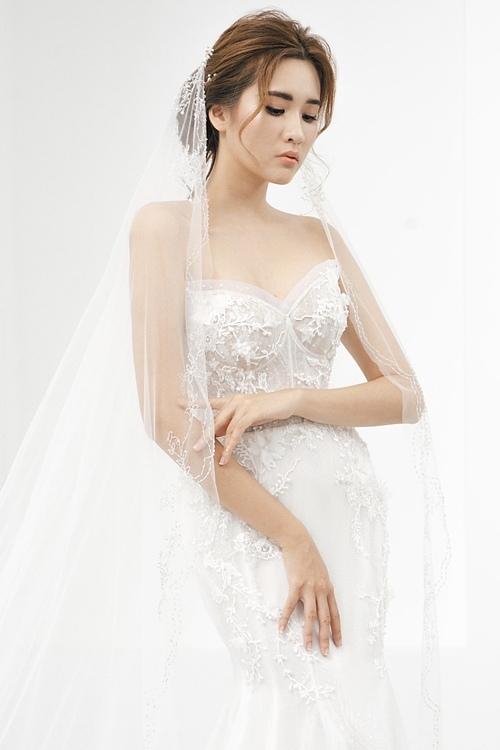 Cô dâu kết hợp cùng khăn voan thêu họa tiết đồng điệu với thân váy để hoàn thiện gu thời trang tinh tế, thanh lịch.