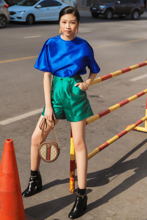 Cô bé dạo phố với bốt, túi xách hàng hiệu, trang phục hai màu xanh lá cây, xanh nước biển.