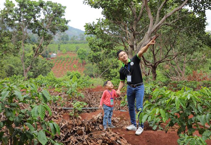Quốc Cơ dẫn con trai tham quan vườn tược của người dân và tìm hiểu về các loài cây được trồng phổ biến ở Tây Nguyên.