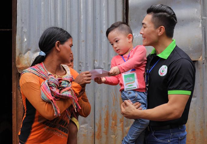 Con trai Quốc Cơ tự trao phong bì tiền cho một phụ nữ nghèo đang nuôi con nhỏ.