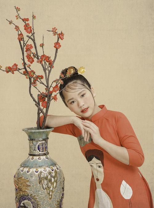 Bella Vũ ra dáng thiếu nữ ở tuổi 12. Cô bé lai hai dòng máu Việt Nam - Singapore, hiện sống ở đảo quốc sư tử nhưng thường xuyên về Việt Nam hoạt động nghệ thuật. Bella Vũ đặc biệt thích quốc phục áo dài.