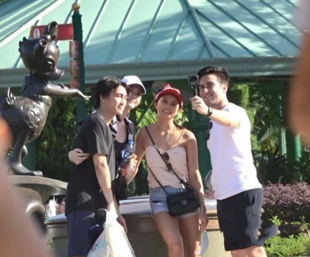 Hà Du Quân và vợ (áo đen, đội mũ) đi Disney Land hôm 28/6.