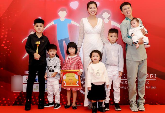 6 con của Oanh Yến đi theo cầm bằng khen và kỷ niệm chương giải thưởng cho mẹ. Chồng Oanh Yến bận công việc nên không có mặt. Stylist Hân Hoan Hỷ - quản lý truyền thông của Oanh Yến (ngoài cùng bên phải) - giúp cô bé con trai út mới gần 3 tháng tuổi.