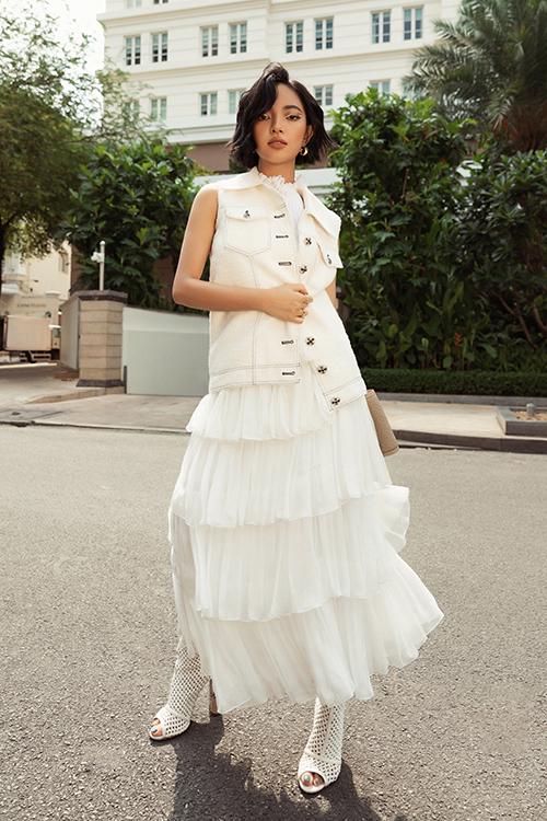 Mẫu váy xếp tầng tông trắng mang hơi hướng phong cách bánh bèo được Châu Bùi xử lý khéo léo trên set đồ bằng cách sử dụng jacket, bốt lưới và clutch Burberry.